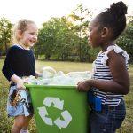 2 little girls carrying a green recycling bin full of plastic bottles